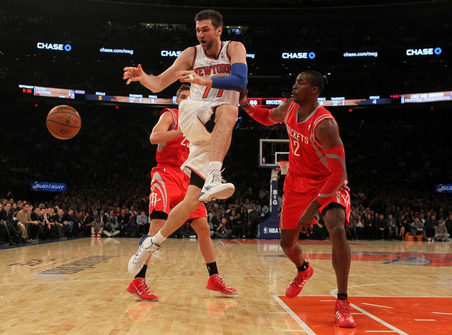 Nov 14, 2013; New York, NY, USA; New York Knicks power forward Andrea Bargnani (77) passes the ball as he drives through Houston Rockets small forward Chandler Parsons (25) and Rockets power forward Dwight Howard (12) during the third quarter of a game at Madison Square Garden. The Rockets beat the Knicks 109-106. Mandatory Credit: Brad Penner-USA TODAY Sports