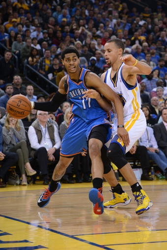 November 14, 2013; Oakland, CA, USA; Oklahoma City Thunder shooting guard Jeremy Lamb (11, left) dribbles the ball against Golden State Warriors point guard Stephen Curry (30, right) during the second quarter at Oracle Arena. Mandatory Credit: Kyle Terada-USA TODAY Sports