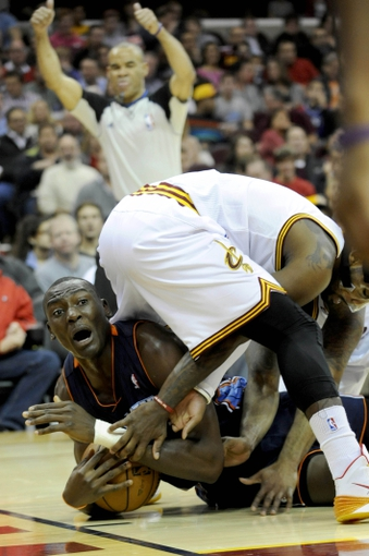 Nov 15, 2013; Cleveland, OH, USA; Charlotte Bobcats center Bismack Biyombo (0) calls time out under the legs of Cleveland Cavaliers point guard Kyrie Irving (2) during the first quarter at Quicken Loans Arena. Mandatory Credit: Ken Blaze-USA TODAY Sports