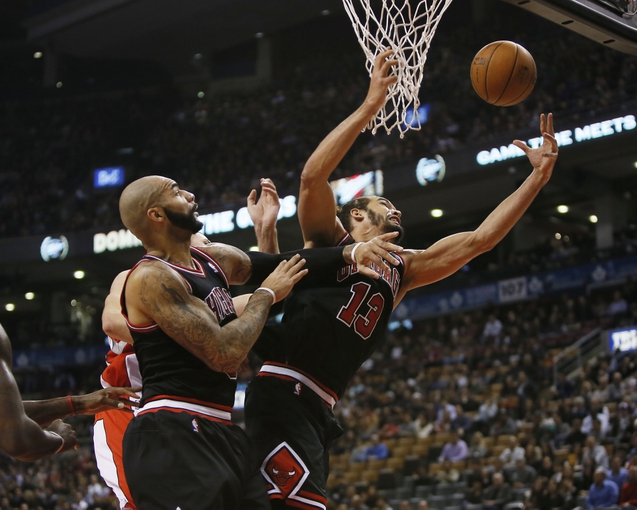Nov 15, 2013; Toronto, Ontario, CAN; Chicago Bulls center Joakim Noah (13) and Chicago Bulls forward Carlos Boozer (5) go up for a rebound against the Toronto Raptors during the first half at the Air Canada Centre. Mandatory Credit: John E. Sokolowski-USA TODAY Sports