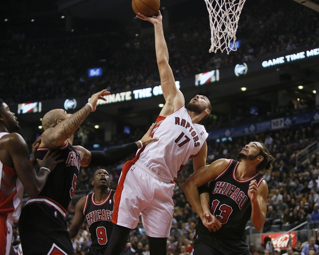 Nov 15, 2013; Toronto, Ontario, CAN; Toronto Raptors center Jonas Valanciunas (17) goes up for a rebound as Chicago Bulls center Joakim Noah (13) and forward Carlos Boozer (5) and forward Luol Deng (9) defend during the first half at the Air Canada Centre. Mandatory Credit: John E. Sokolowski-USA TODAY Sports