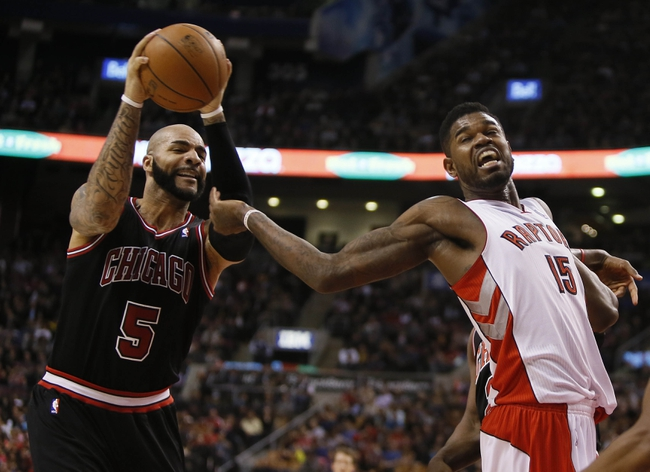 Nov 15, 2013; Toronto, Ontario, CAN; Chicago Bulls forward Carlos Boozer (5) gets a rebound from Toronto Raptors forward-center Amir Johnson (15) during the first half at the Air Canada Centre. Mandatory Credit: John E. Sokolowski-USA TODAY Sports