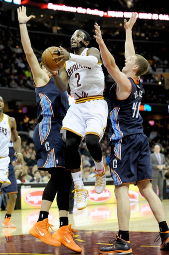 Nov 15, 2013; Cleveland, OH, USA; Cleveland Cavaliers point guard Kyrie Irving (2) drives between Charlotte Bobcats center Cody Zeller (40) and Charlotte Bobcats power forward Josh McRoberts (11) during the second quarter at Quicken Loans Arena. Mandatory Credit: Ken Blaze-USA TODAY Sports