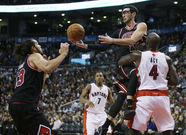 Nov 15, 2013; Toronto, Ontario, CAN; Chicago Bulls guard Kirk Hinrich (12) passes to Joakim Noah (13) as Toronto Raptors forward Quincy Acy (4) and guard Kyle Lowry (7) defend at the Air Canada Centre. Chicago defeated Toronto 96-80. Mandatory Credit: John E. Sokolowski-USA TODAY Sports