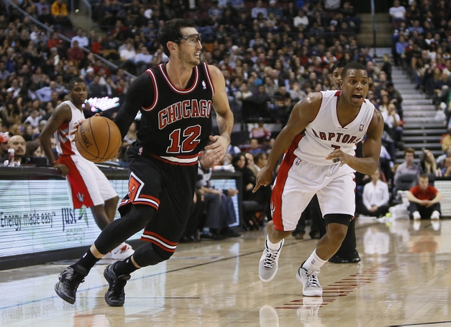 Nov 15, 2013; Toronto, Ontario, CAN; Chicago Bulls guard Kirk Hinrich (12) carries the ball past Toronto Raptors guard Kyle Lowry (7) at the Air Canada Centre. Chicago defeated Toronto 96-80. Mandatory Credit: John E. Sokolowski-USA TODAY Sports