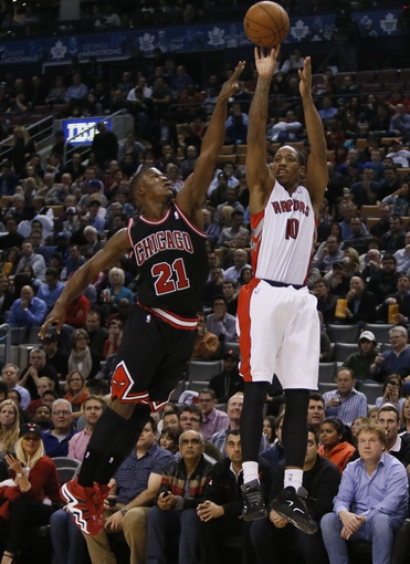 Nov 15, 2013; Toronto, Ontario, CAN; Toronto Raptors guard DeMar DeRozan (10) shoots as Chicago Bulls guard-forward Jimmy Butler (21) defends during the first half at the Air Canada Centre. Mandatory Credit: John E. Sokolowski-USA TODAY Sports