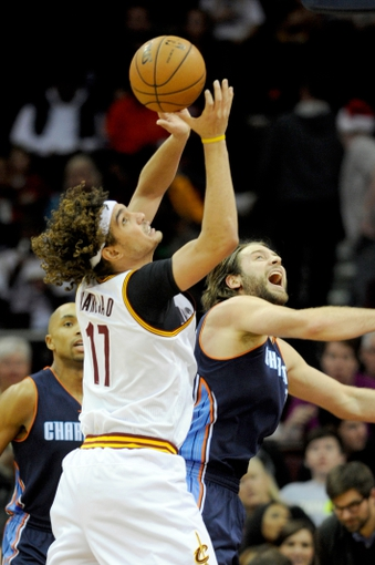 Nov 15, 2013; Cleveland, OH, USA; Cleveland Cavaliers center Anderson Varejao (17) grabs a rebound over Charlotte Bobcats power forward Josh McRoberts (11) during the third quarter at Quicken Loans Arena. The Bobcats beat the Cavaliers 86-80. Mandatory Credit: Ken Blaze-USA TODAY Sports