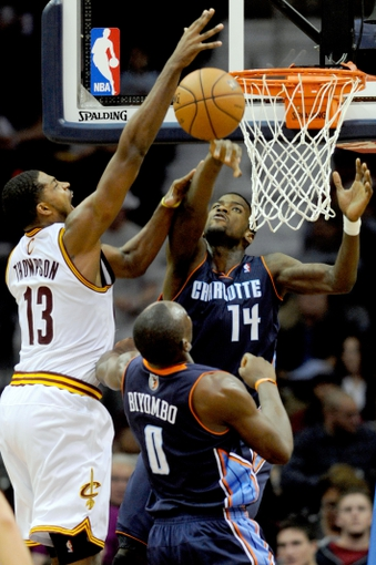 Nov 15, 2013; Cleveland, OH, USA; Charlotte Bobcats small forward Michael Kidd-Gilchrist (14) and Charlotte Bobcats center Bismack Biyombo (0) defend the shot by Cleveland Cavaliers power forward Tristan Thompson (13) during the third quarter at Quicken Loans Arena. The Bobcats beat the Cavaliers 86-80. Mandatory Credit: Ken Blaze-USA TODAY Sports