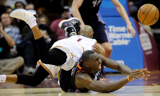 Nov 15, 2013; Cleveland, OH, USA; Cleveland Cavaliers point guard Jarrett Jack (1) falls on Charlotte Bobcats center Bismack Biyombo (0) as Biyombo gets the ball away during the third quarter at Quicken Loans Arena. The Bobcats beat the Cavaliers 86-80. Mandatory Credit: Ken Blaze-USA TODAY Sports