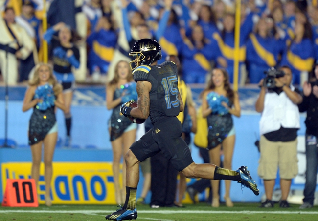 Nov 15, 2013; Pasadena, CA, USA; UCLA Bruins receiver Devin Lucien (15) scores on a 40-yard touchdown reception against the Washington Huskies at Rose Bowl. UCLA defeated Washington 41-31.  Mandatory Credit: Kirby Lee-USA TODAY Sports