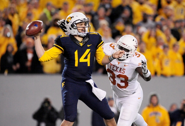 Nov 9, 2013; Morgantown, WV, USA; West Virginia Mountaineers quarterback Paul Millard (14) throws the ball while getting pressured by Texas Longhorns linebacker Steve Edmond (33) at Milan Puskar Stadium. Mandatory Credit: Evan Habeeb-USA TODAY Sports