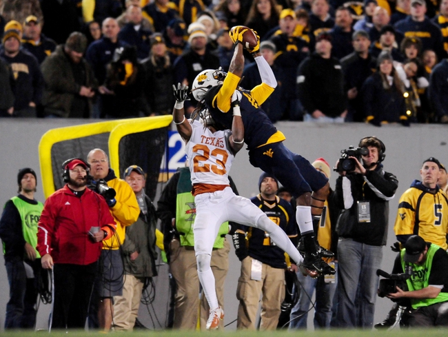 Nov 9, 2013; Morgantown, WV, USA; West Virginia Mountaineers wide receiver Kevin White (11) catches a pass over Texas Longhorns cornerback Carrington Byndom (23) at Milan Puskar Stadium. Mandatory Credit: Evan Habeeb-USA TODAY Sports