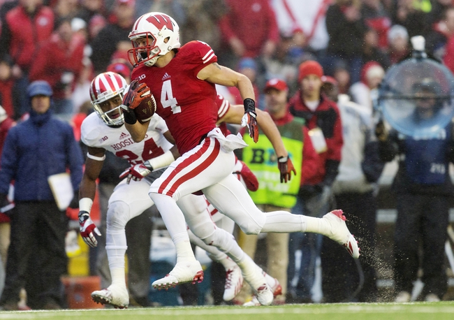 Nov 16, 2013; Madison, WI, USA; Wisconsin Badgers wide receiver Jared Abbrederis (4) runs for a touchdown during the second quarter past Indiana Hoosiers defensive back Tim Bennett (24) at Camp Randall Stadium. Mandatory Credit: Jeff Hanisch-USA TODAY Sports