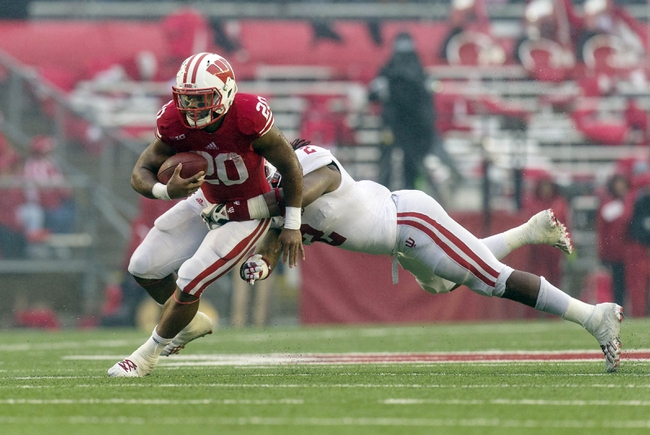 Nov 16, 2013; Madison, WI, USA; Wisconsin Badgers running back James White (20) carries the football as Indiana Hoosiers linebacker T.J. Simmons (2) dives to make the tackle during the second quarter at Camp Randall Stadium. Mandatory Credit: Jeff Hanisch-USA TODAY Sports
