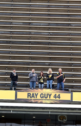 Nov 16, 2013; Hattiesburg, MS, USA; Southern Miss Golden Eagles fans stand during the playing of the National Anthem in front of a sign honoring alumni Ray Guy before the start of their game against the Florida Atlantic Owls  at M.M. Roberts Stadium. Mandatory Credit: Chuck Cook-USA TODAY Sports
