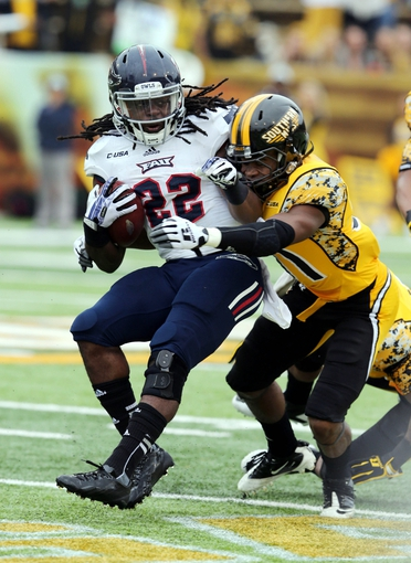 Nov 16, 2013; Hattiesburg, MS, USA; Florida Atlantic Owls running back Damian Fortner (22) is tackled by Southern Miss Golden Eagles defensive back Alexander Walters (31) during the first half at M.M. Roberts Stadium. Mandatory Credit: Chuck Cook-USA TODAY Sports