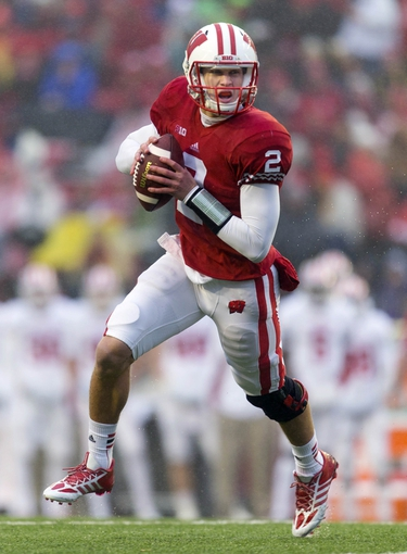 Nov 16, 2013; Madison, WI, USA; Wisconsin Badgers quarterback Joel Stave (2) rolls out of the pocket during the third quarter against the Indiana Hoosiers at Camp Randall Stadium. Wisconsin won 51-3.  Mandatory Credit: Jeff Hanisch-USA TODAY Sports