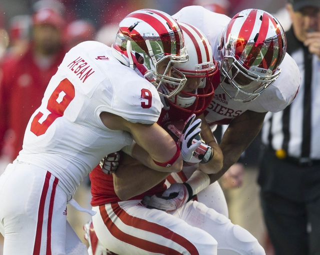 Nov 16, 2013; Madison, WI, USA; Wisconsin Badgers wide receiver Alex Erickson (86) is tackled by Indiana Hoosiers safety Greg Heban (9  during the fourth quarter against the Indiana Hoosiers at Camp Randall Stadium. Mandatory Credit: Jeff Hanisch-USA TODAY Sports