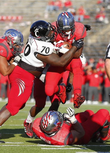 Nov 16, 2013; Piscataway, NJ, USA;  Cincinnati Bearcats defensive lineman Brandon Mitchell (70) wraps up Rutgers Scarlet Knights running back Savon Huggins (ball) as he hurdles offensive linesman Chris Muller (on ground) at High Points Solutions Stadium. Cincinnati Bearcats defeat the Rutgers Scarlet Knights 52-17. Mandatory Credit: Jim O'Connor-USA TODAY Sports