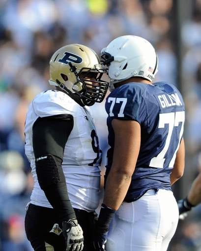 Nov 16, 2013; University Park, PA, USA; Purdue Boilermakers defensive tackle Bruce Gaston (90) and Penn State Nittany Lions offensive tackle Garry Gilliam (77) stand face to face while their helmets are locked together during the third quarter at Beaver Stadium.  Penn State defeated Purdue  45-21.  Mandatory Credit: Rich Barnes-USA TODAY Sports