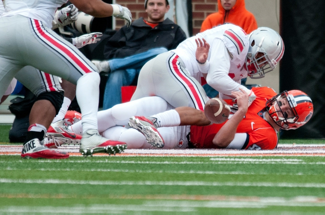Nov 16, 2013; Champaign, IL, USA;  Illinois Fighting Illini quarterback Reilly O'Toole (4) fumbles the ball during the third quarter against the Ohio State Buckeyes at Memorial Stadium.   The play resulted in a safety.  Mandatory Credit: Bradley Leeb-USA TODAY Sports