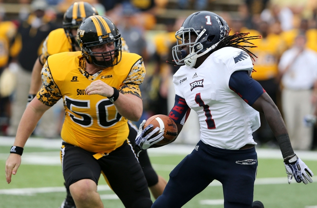 Nov 16, 2013; Hattiesburg, MS, USA; Florida Atlantic Owls kick returner Lucky Whitehead (1) runs with the ball as Southern Miss long snapper Lance Schuffert (50) defends during the second half at M.M. Roberts Stadium. Florida Atlantic won 41-7. Mandatory Credit: Chuck Cook-USA TODAY Sports