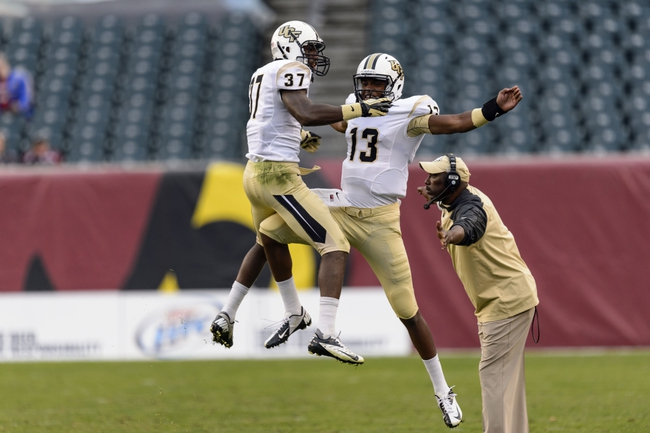 Nov 16, 2013; Philadelphia, PA, USA; UCF Knights defensive back Brandon Alexander (37) celebrates making an interception with quarterback Justin Holman (13) during the fourth quarter against the Temple Owls at Lincoln Financial Field. UCF defeated Temple 39-36. Mandatory Credit: Howard Smith-USA TODAY Sports