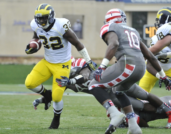 Nov 16, 2013; Evanston, IL, USA; Michigan Wolverines running back De'Veon Smith (32) runs with the ball as Northwestern Wildcats linebacker Damien Proby (46) tackles during the first half at Ryan Field. Mandatory Credit: David Banks-USA TODAY Sports