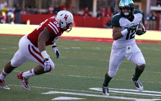 Nov 16, 2013; Lincoln, NE, USA; Michigan State Spartans receiver R.J. Shelton (12) heads to the end zone against the Nebraska Cornhuskers defender Arron Curry (96) in the first quarter at Memorial Stadium. Mandatory Credit: Bruce Thorson-USA TODAY Sports