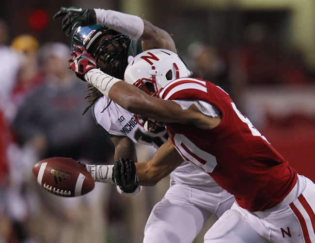 Nov 16, 2013; Lincoln, NE, USA; Michigan State Spartans defender Trae Waynes (15) breaks up the pass intended for Nebraska Cornhuskers receiver Kenny Bell (80) in the third quarter at Memorial Stadium. Mandatory Credit: Bruce Thorson-USA TODAY Sports