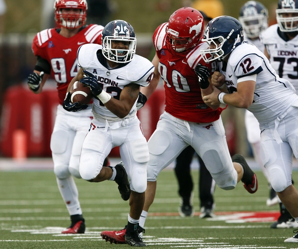 Nov 16, 2013; Dallas, TX, USA; Connecticut Huskies running back Lyle McCombs (43) rushes in front of Southern Methodist Mustangs defensive end Zach Wood (90) during the second half on an NCAA football game at Gerald J. Ford Stadium. Southern Methodist Mustangs won 38-21. Mandatory Credit: Jim Cowsert-USA TODAY Sports