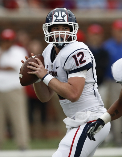 Nov 16, 2013; Dallas, TX, USA; Connecticut Huskies quarterback Casey Cochran (12) sets to pass against the Connecticut Huskies during the second half on an NCAA football game at Gerald J. Ford Stadium. Southern Methodist Mustangs won 38-21. Mandatory Credit: Jim Cowsert-USA TODAY Sports