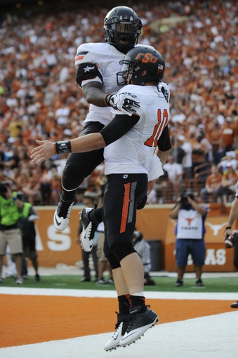 Nov 16, 2013; Austin, TX, USA; Oklahoma State Cowboys quarterback Clint Chelf (10) and running back Rennie Childs (l) celebrate after scoring a touchdown against the Texas Longhorns during the first quarter at Darrell