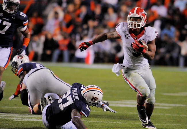 Nov 16, 2013; Auburn, AL, USA; Georgia Bulldogs running back Todd Gurley (3) runs the ball past the Auburn Tigers defense during the second half at Jordan Hare Stadium. The Tigers defeated the Bulldogs 43-38. Mandatory Credit: Shanna Lockwood-USA TODAY Sports