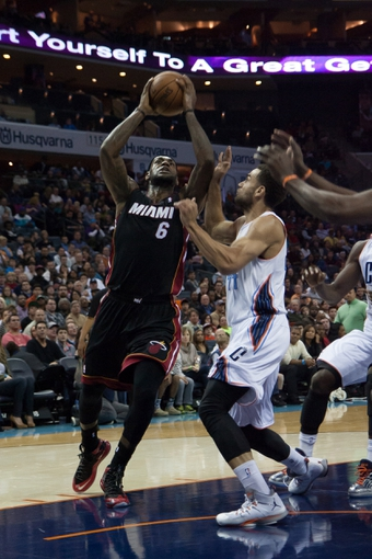 Nov 16, 2013; Charlotte, NC, USA; Miami Heat small forward LeBron James (6) goes up for a shot while Charlotte Bobcats shooting guard Jeff Taylor (44) defends during the first half at Time Warner Cable Arena. Mandatory Credit: Jeremy Brevard-USA TODAY Sports