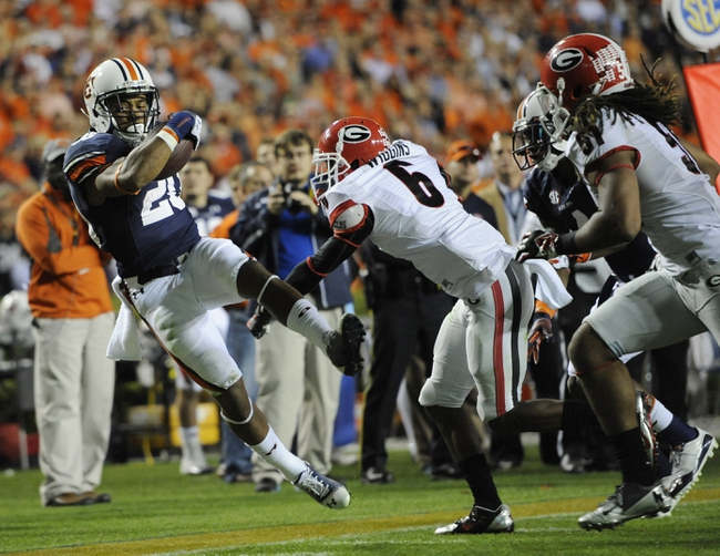 Nov 16, 2013; Auburn, AL, USA; Auburn Tigers running back Corey Grant (20) is knocked out-of-bounds by Georgia Bulldogs cornerback Shaq Wiggins (6) during the second half  at Jordan Hare Stadium. The Tigers defeated the Bulldogs 43-38. Mandatory Credit: Shanna Lockwood-USA TODAY Sports