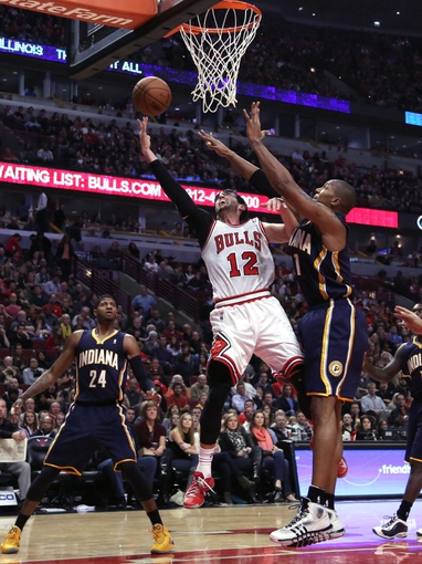 Nov 16, 2013; Chicago, IL, USA; Chicago Bulls shooting guard Kirk Hinrich (12) scores past Indiana Pacers power forward David West (21) during the second quarter at  the United Center. Mandatory Credit: Dennis Wierzbicki-USA TODAY Sports
