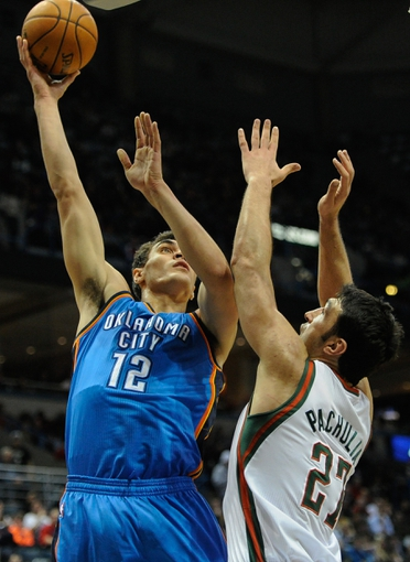 Nov 16, 2013; Milwaukee, WI, USA; Oklahoma City Thunder center Steven Adams (12) shoots over Milwaukee Bucks center Zaza Pachulia (27) in the 2nd quarter at BMO Harris Bradley Center. Mandatory Credit: Benny Sieu-USA TODAY Sports