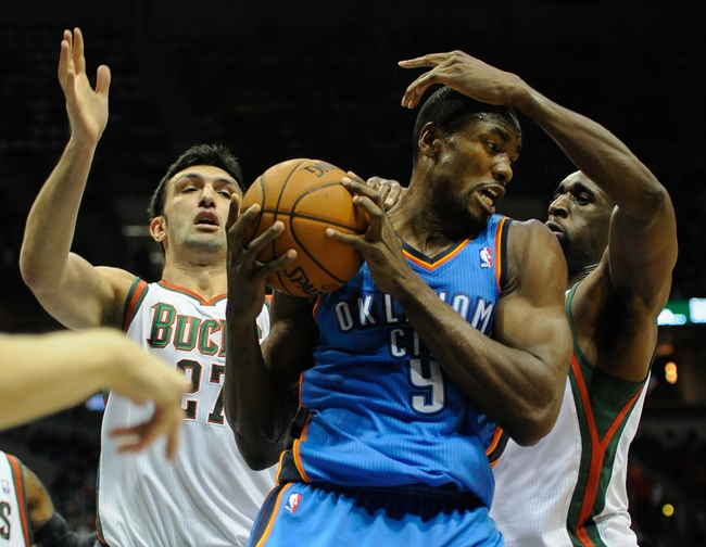 Nov 16, 2013; Milwaukee, WI, USA;   Oklahoma City Thunder forward Serge Ibaka (9) grabs a rebound between Milwaukee Bucks center Zaza Pachulia (27) and forward Ekpe Udoh (5) in the 2nd quarter at BMO Harris Bradley Center. Mandatory Credit: Benny Sieu-USA TODAY Sports