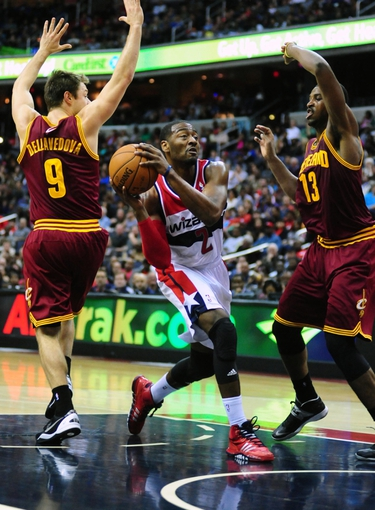 Nov 16, 2013; Washington, DC, USA; Washington Wizards guard John Wall (2) drives to the basket while being guarded by Cleveland Cavaliers guard Matthew Dellavedova (9) and forward Tristan Thompson (13) at Verizon Center. Mandatory Credit: Evan Habeeb-USA TODAY Sports