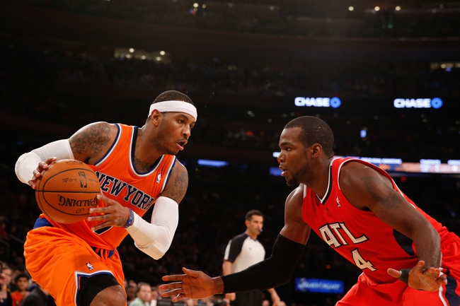 Nov 16, 2013; New York, NY, USA;  Atlanta Hawks power forward Paul Millsap (4) defends against New York Knicks small forward Carmelo Anthony (7) during the third quarter at Madison Square Garden. Atlanta Hawks won 110-90.  Mandatory Credit: Anthony Gruppuso-USA TODAY Sports