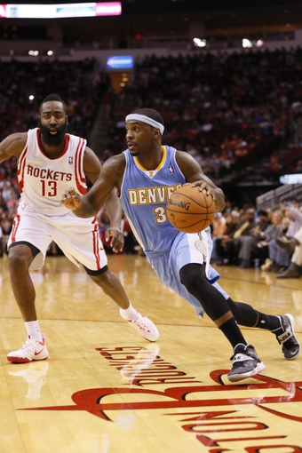 Nov 16, 2013; Houston, TX, USA; Denver Nuggets guard Ty Lawson (3) dribbles the ball as Houston Rockets guard James Harden (13) defends during the second half at Toyota Center. The Rockets won 122-111. Mandatory Credit: Soobum Im-USA TODAY Sports