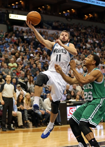 Nov 16, 2013; Minneapolis, MN, USA; Minnesota Timberwolves point guard J.J. Barea (11) goes up for a layup past Boston Celtics point guard Phil Pressey (26) in the second half at Target Center. The Timberwolves won 106-88. Mandatory Credit: Jesse Johnson-USA TODAY Sports