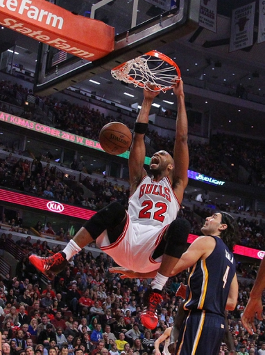 Nov 16, 2013; Chicago, IL, USA; Chicago Bulls power forward Taj Gibson (22) dunks over Indiana Pacers power forward Luis Scola (4) during the second half at  the United Center. Chicago won 110-94. Mandatory Credit: Dennis Wierzbicki-USA TODAY Sports