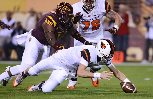 Nov 16, 2013; Tempe, AZ, USA; Oregon State Beavers quarterback Sean Mannion (4) recovers his own fumble against Arizona State Sun Devils defensive lineman Marcus Hardison (1) in the first half of the game at Sun Devil Stadium. Mandatory Credit: Jennifer Stewart-USA TODAY Sports