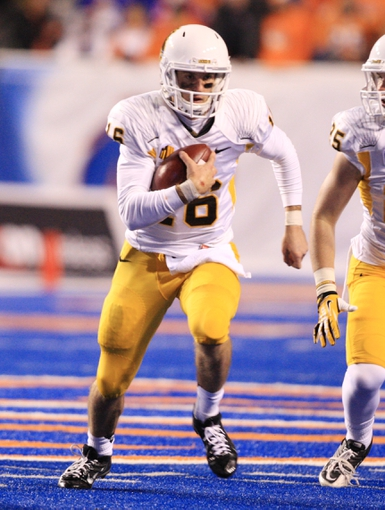 Nov 16, 2013; Boise, ID, USA; Wyoming Cowboys quarterback Brett Smith (16) scrambles for yardage during  first half of play verses the Boise State Broncos at Bronco Stadium. Mandatory Credit: Brian Losness-USA TODAY Sports