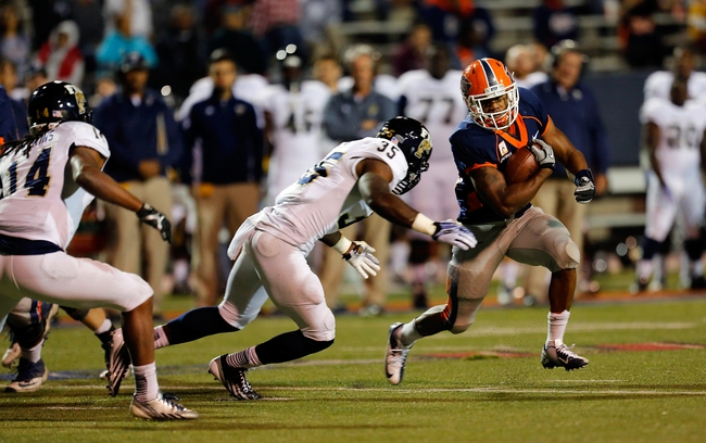 Nov 16, 2013; El Paso, TX, USA; UTEP Miners running back Josh Bell (23) tries to break a tackle against FIU Golden Panthers linebacker Davison Colimon (35) at Sun Bowl Stadium. Mandatory Credit: Ivan Pierre Aguirre-USA TODAY Sports