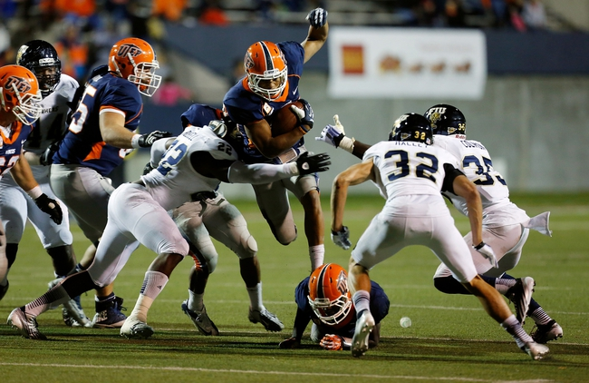 Nov 16, 2013; El Paso, TX, USA; UTEP Miners running back Nathan Jeffery (25) tries to break a tackle from FIU Golden Panthers linebacker Markeith Russell (22) at Sun Bowl Stadium. Mandatory Credit: Ivan Pierre Aguirre-USA TODAY Sports