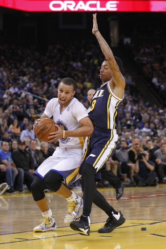 Nov 16, 2013; Oakland, CA, USA; Golden State Warriors guard Stephen Curry (30) drives past Utah Jazz guard Diante Garrett (8) in the first quarter at Oracle Arena. Mandatory Credit: Cary Edmondson-USA TODAY Sports