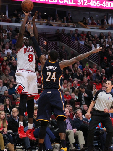 Nov 16, 2013; Chicago, IL, USA; Chicago Bulls small forward Luol Deng (9) scores over Indiana Pacers small forward Paul George (24) during the second half at  the United Center. Chicago won 110-94. Mandatory Credit: Dennis Wierzbicki-USA TODAY Sports